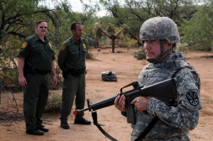 Border Patrol agents observe an Arizona National Guardsman training in the desert. (U.S. Army photo by