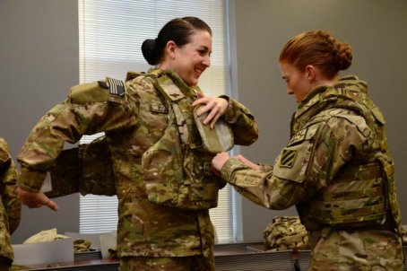 Pvt. 1st Class Cheryl Rogers grins as 2nd Lt. Chelsea Adams helps her into the new Generation III Female Improved Outer Tactical Vest, Nov. 28. (U.S. Army photo by Cpl. Emily Knitter)