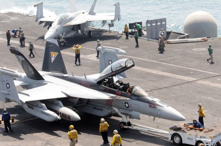 Sailors maneuver an E/A-18G Growler aircraft assigned to Tactical Electronic Warfare Squadron (VAQ) 141 on the flight deck of the aircraft carrier USS George H.W. Bush (CVN 77) in 2011.  (U.S. Navy photo by Mass Communication Specialist Seaman K. Cecelia Engrums)