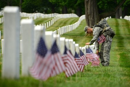 Army Sgt. Titus Fields of the 3rd U.S. Infantry Regiment -- The Old Guard -- places an American flag in front of a gravestone in Arlington National Cemetery, Arlington, Va., May 23, 2013. (U.S. Army photo by Sgt. Jose A. Torres Jr.)