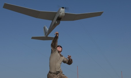 A Marine launches a Puma UAV by hand in Afghanistan. (Photo by Sgt. Bobby J. Yarbrough)