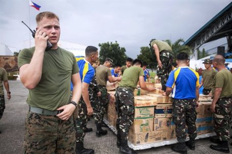 Marine Lance Cpl. Christopher Pring coordinates the loading of pallets of water with the Philippine Air Force for transport at Vilamor Air Base in Manila. (U.S. Marine Corps photo by Cpl. Codey Underwood)