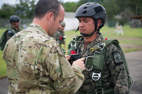 A Green Beret from 7th Special Forces Group inspects a soldier from the 15th Fuerzas Especiales Battalion, at Soto Cano Air Base, Honduras during a joint airborne exercise. (U.S. Army photo by Spc. Steven K. Young)