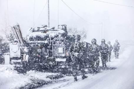 A Swedish squad struggles through the weather on patrol. In the background is a Swedish CV90 infantry fighting vehicle.  (Photo credit: Lars Magne Hovtun, Norwegian Armed Forces)
