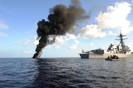 USS Farragut (DDG 99) passes by the smoke from a suspected pirate skiff. (U.S. Navy photo)