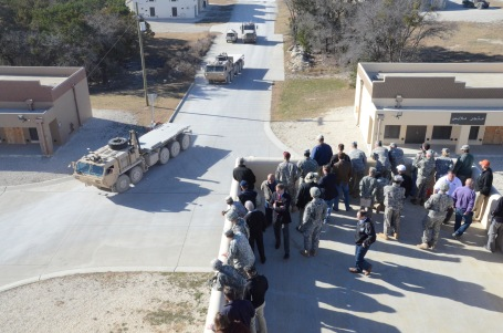 VIPs watch a convoy of driverless trucks at the Autonomous Mobility Applique System demonstration from roof at the Urban Terrain training site at Fort Hood, Texas. (U.S. Army photo)