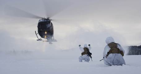 Norwegin troops guide a Bell 412SP helicopter in during Exercise Joint Viking. (Norwegian Armed Forces photo)