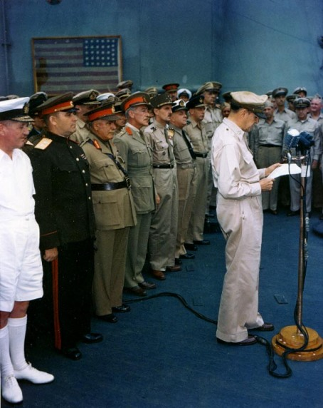 General of the Army Douglas MacArthur, Supreme Allied Commander, reading his speech to open the surrender ceremonies, on board USS Missouri. Commodore Perry's 1853 flag hangs in the background.