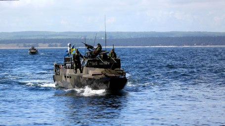 Armored vehicles loaded with troops hit the beach in Sweeden during BALTOPS 2015
