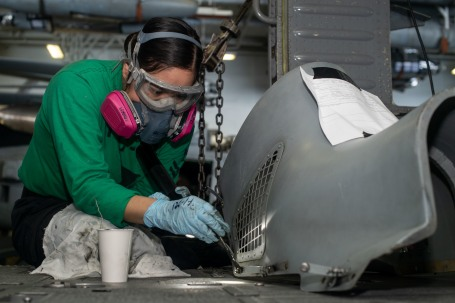 U.S. Sailor paints a cowling for an MH-60S Sea Hawk